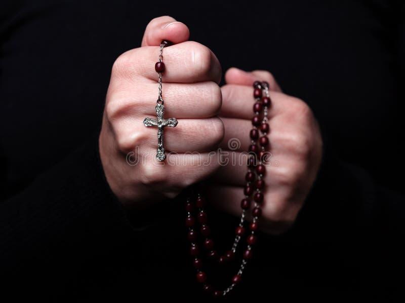 祈祷女性的手拿着有耶稣基督的一个念珠十字架或耶稣受难象的在黑背景 库存图片