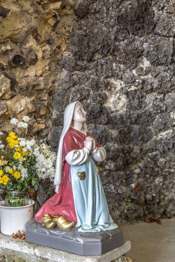 祈祷对我们的卢尔德的夫人的贝尔纳黛特雕象有花的在她旁边 免版税图库摄影