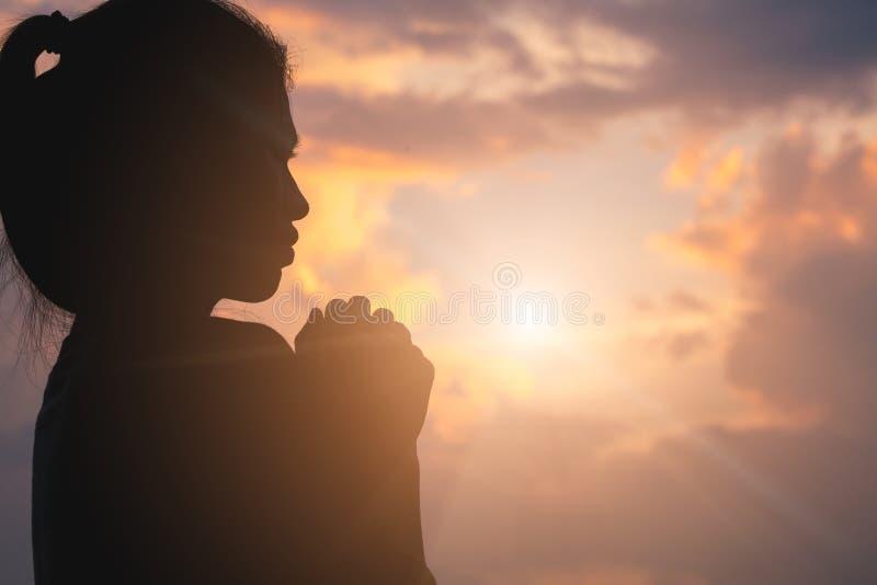 祈祷对神的年轻人的手剪影在日出,基督徒宗教概念背景 免版税库存图片