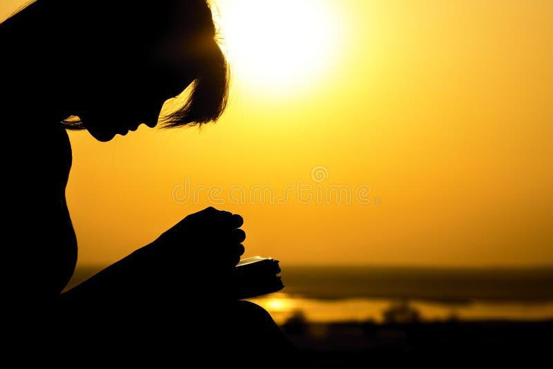 祈祷对自然witth的上帝圣经的妇女的手的剪影在日落、宗教的概念和灵性 免版税库存图片