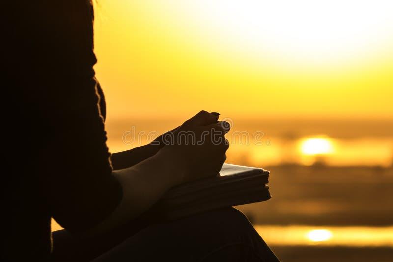祈祷对自然witth的上帝圣经的妇女的手的剪影在日落、宗教的概念和灵性 免版税库存照片