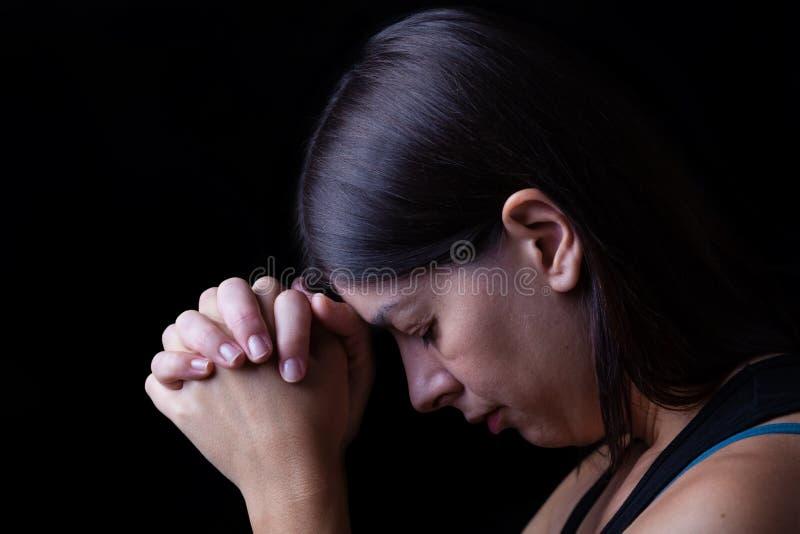 祈祷忠实的妇女,手在崇拜折叠了给神 库存图片