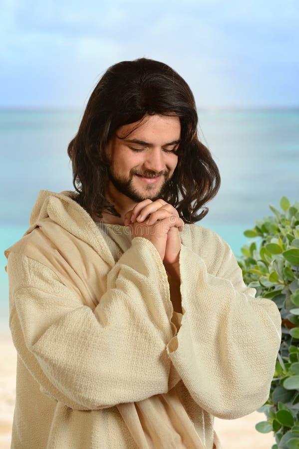 祈祷由海的耶稣 免版税库存照片