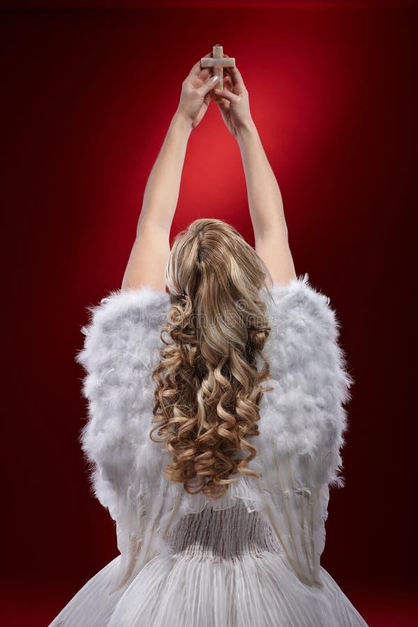 祈祷的天使拿着耶稣受难象 免版税图库摄影