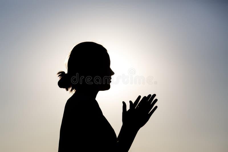 祈祷的妇女剪影在日出的 库存照片
