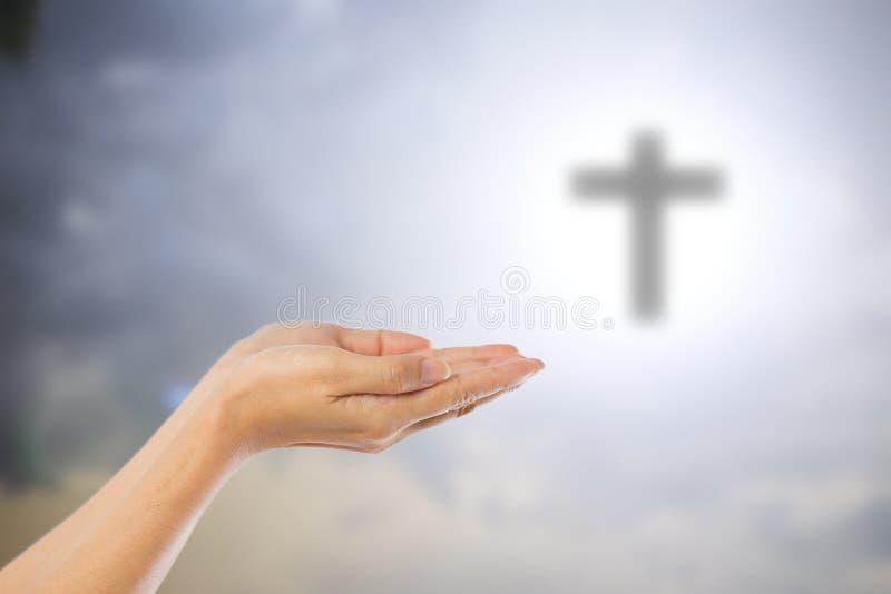 祈祷的妇女的手弄脏了在天空backgro的十字架 免版税库存图片