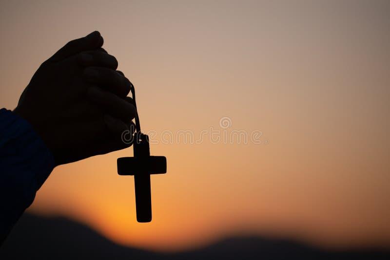 祈祷的妇女,当拿着十字架时,早晨,一起祈祷用手的妇女祈祷在日出背景 库存图片