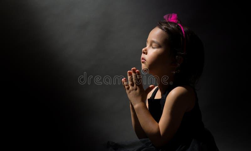 祈祷的小女孩,被隔绝的黑背景 库存图片