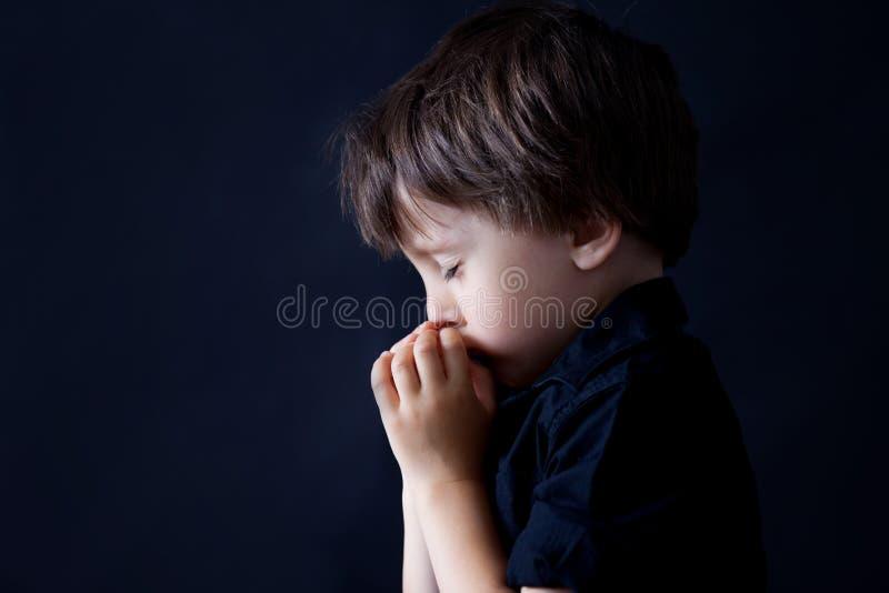 祈祷的小男孩,祈祷的孩子,背景 免版税库存图片