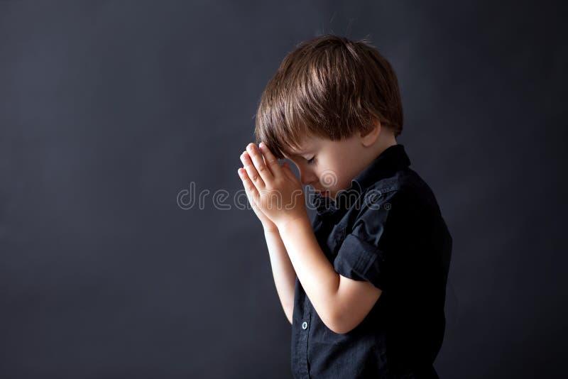 祈祷的小男孩,祈祷的孩子,被隔绝的背景 免版税库存照片