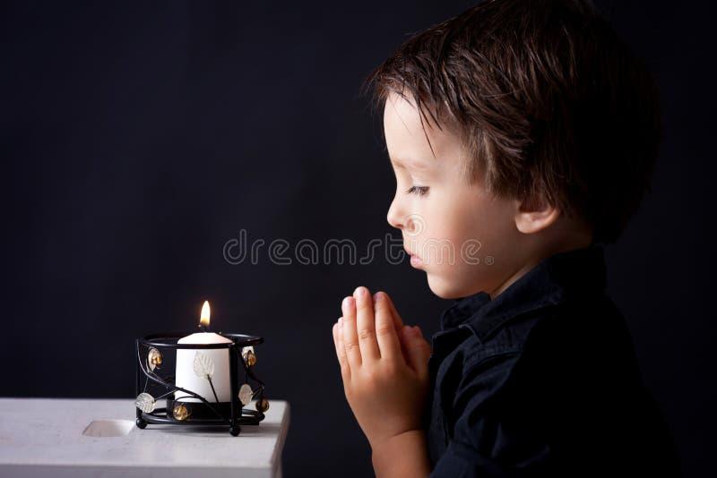 祈祷的小男孩,祈祷的孩子,被隔绝的背景 免版税图库摄影