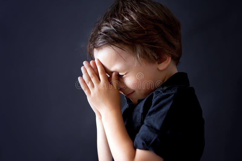 祈祷的小男孩,祈祷的孩子,被隔绝的背景 库存图片