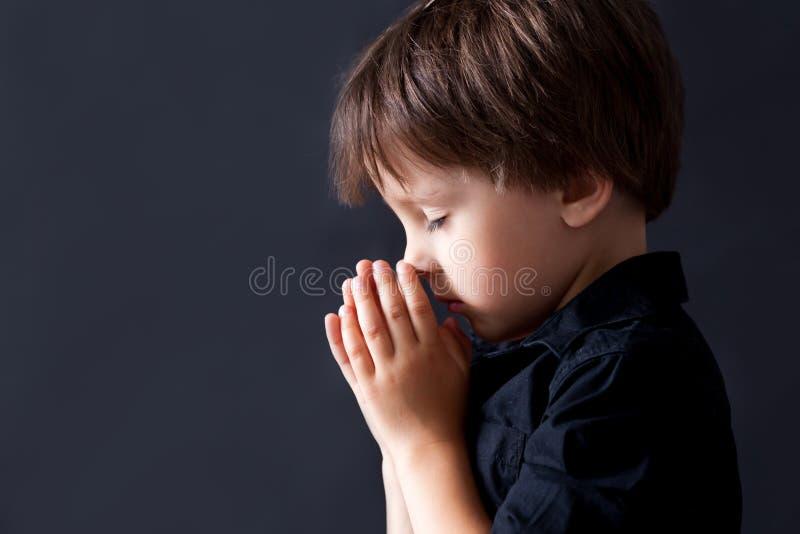 祈祷的小男孩,祈祷的孩子,被隔绝的背景 免版税库存图片