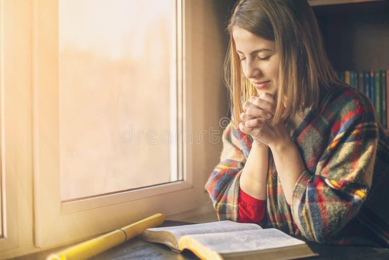 祈祷的美女有在窗口前面被打开的圣经 免版税库存图片