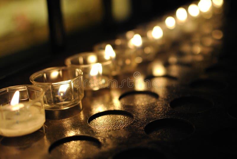 祈祷的蜡烛在大教堂里 库存图片