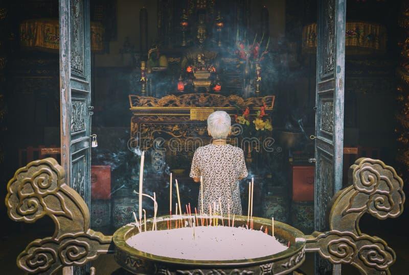 祈祷菩萨的资深妇女在寺庙 库存图片