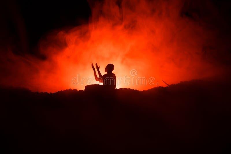 祈祷被定调子的有雾的背景的回教人剪影  赖买丹月Kareem背景 穆斯林Eid假日装饰 祈祷的peop 库存图片
