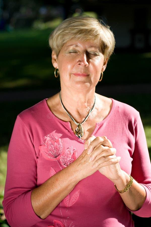 祈祷高级妇女 免版税图库摄影