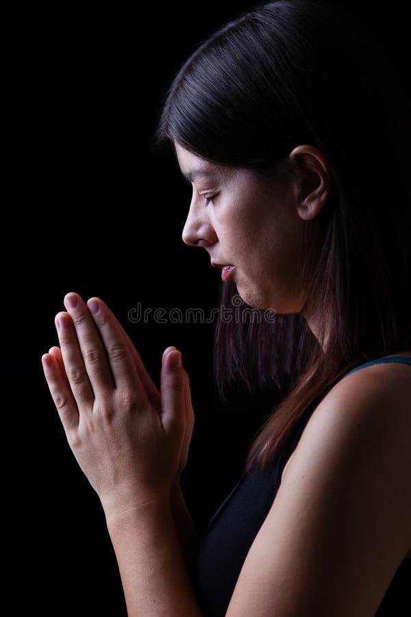 祈祷,当手的忠实的妇女被折叠在崇拜对神 免版税库存照片