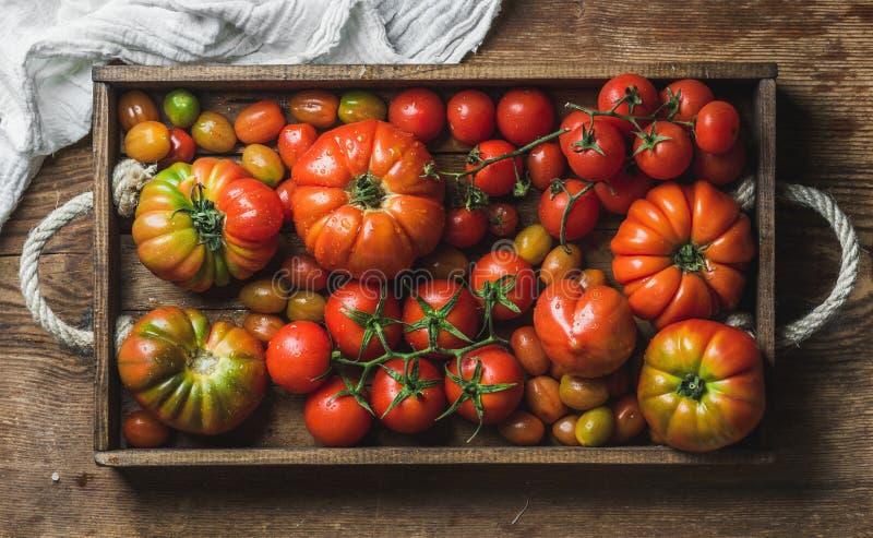祖传遗物、束和西红柿的五颜六色的分类在土气盘子在木背景 免版税图库摄影