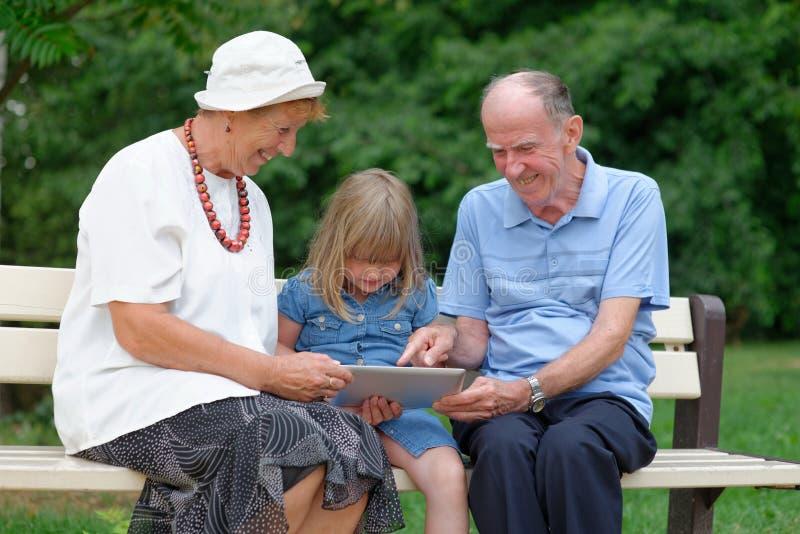 祖母、使用片剂的祖父和孙女 库存照片