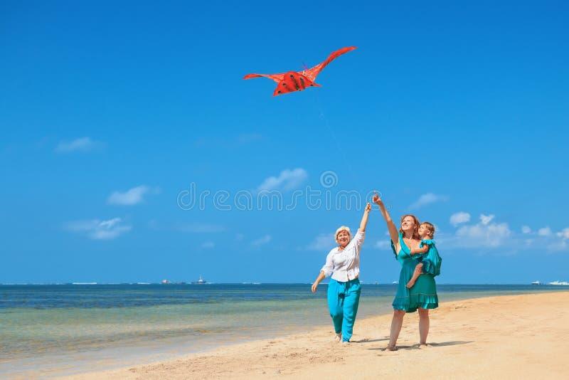 祖母、母亲和儿童发射的风筝在海洋海滩 免版税图库摄影