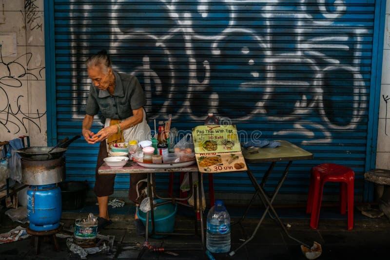 祖母准备垫泰语用鸡蛋的一个不明身份的摊位供营商 在她的排档 r 免版税库存图片