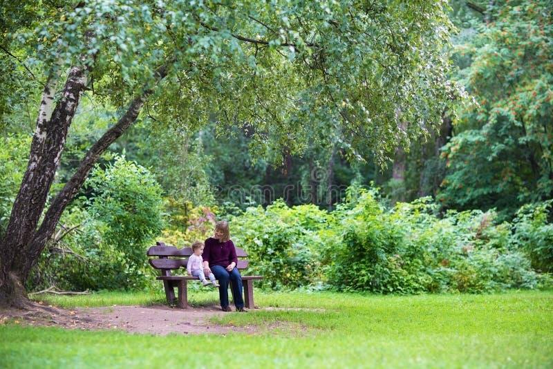 祖母和女婴在长凳的公园在大树下 免版税库存图片