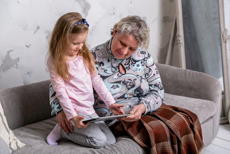 祖母和她的小孙女一起是电影和使用在设备,当坐沙发时 库存照片