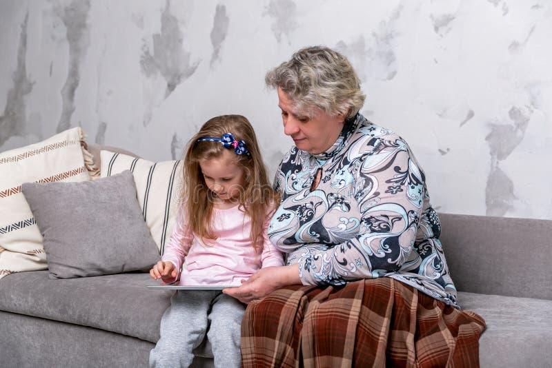 祖母和她的小孙女一起是电影和使用在设备,当坐沙发时 免版税库存照片
