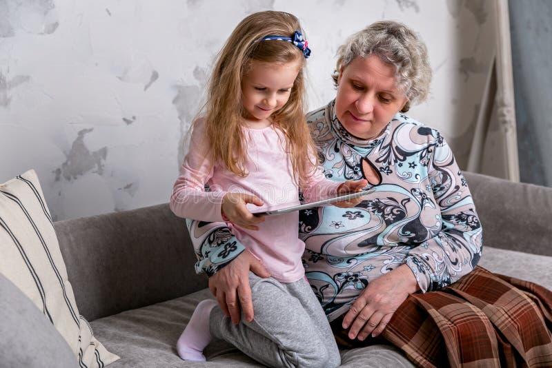 祖母和她的小孙女一起是电影和使用在设备,当坐沙发时 免版税图库摄影