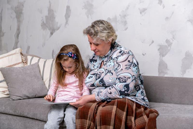 祖母和她的小孙女一起是电影和使用在设备,当坐沙发时 库存图片