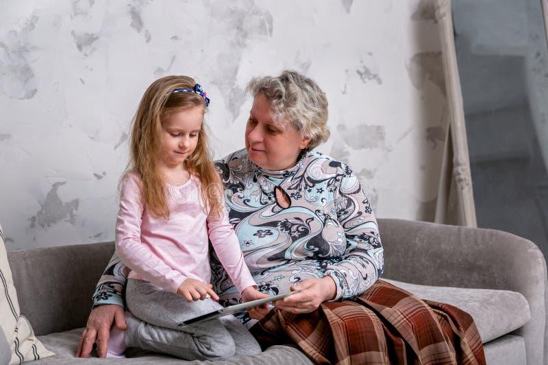 祖母和她的小孙女一起是电影和使用在设备,当坐沙发时 免版税库存图片