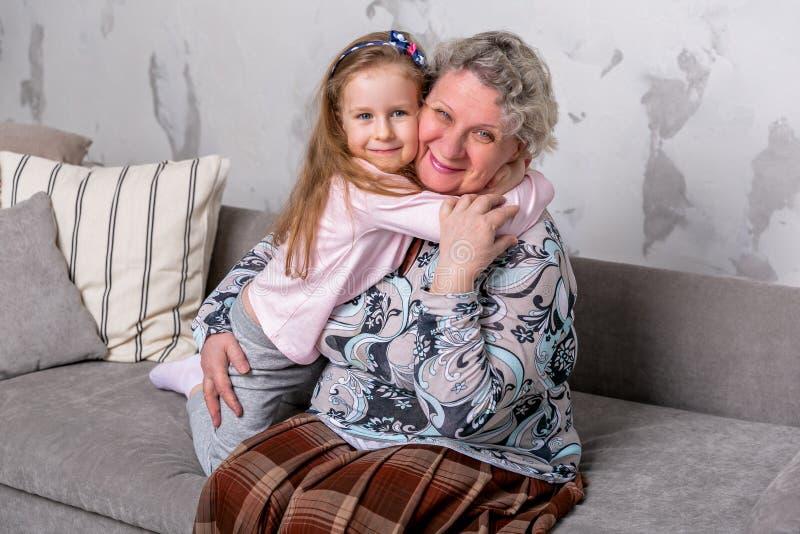 祖母和她的小孙女一起是电影和使用在设备,当坐沙发时 图库摄影