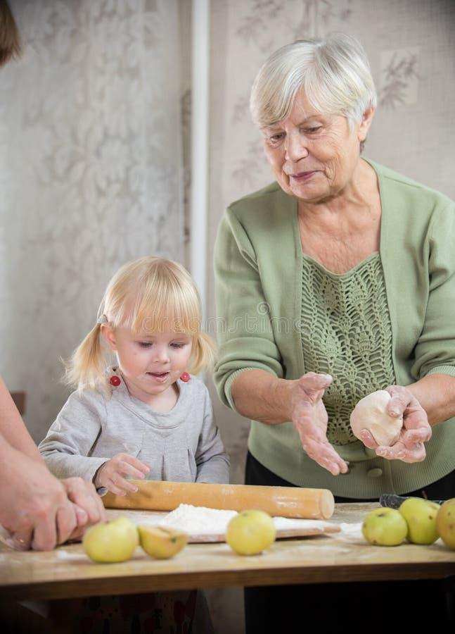 祖母和孙女做小的饼 库存照片