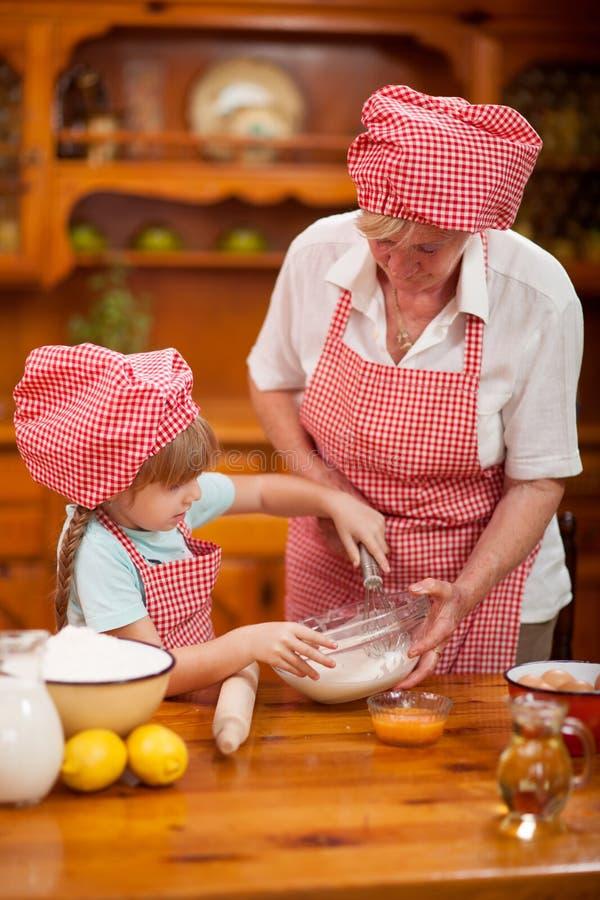 祖母和孙女厨师烘烤在厨房里 库存图片