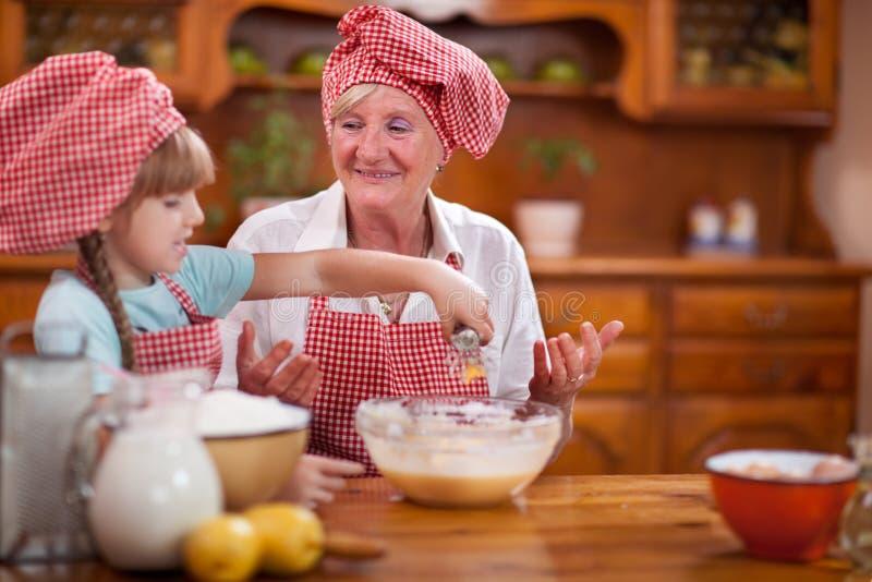 祖母和孙女厨师烘烤在厨房里 库存照片