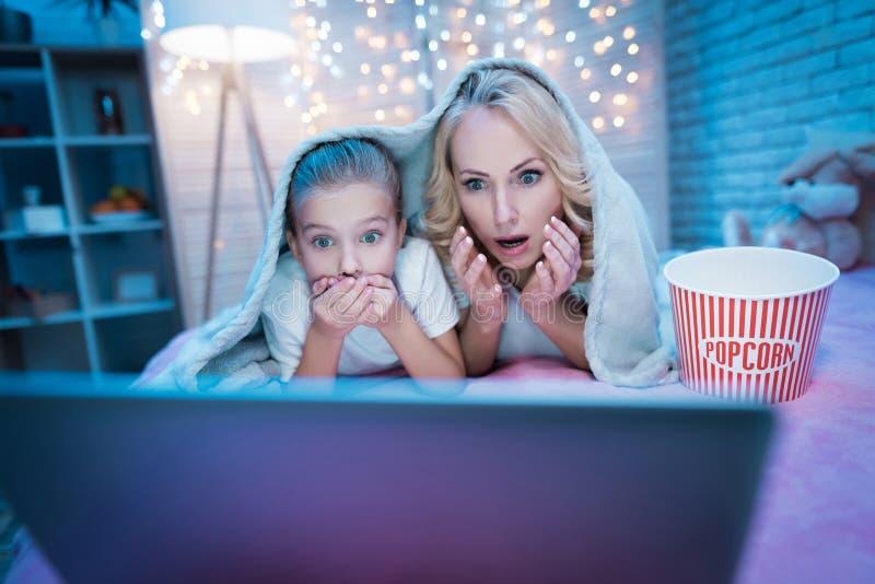 祖母和孙女在晚上在家观看在膝上型计算机的电影 免版税库存照片
