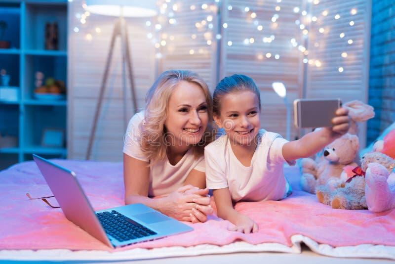 祖母和孙女在晚上在家采取selfie 免版税库存照片