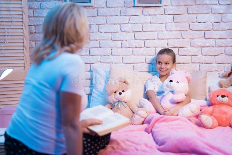 祖母和孙女读童话在晚上在家预定 免版税库存图片