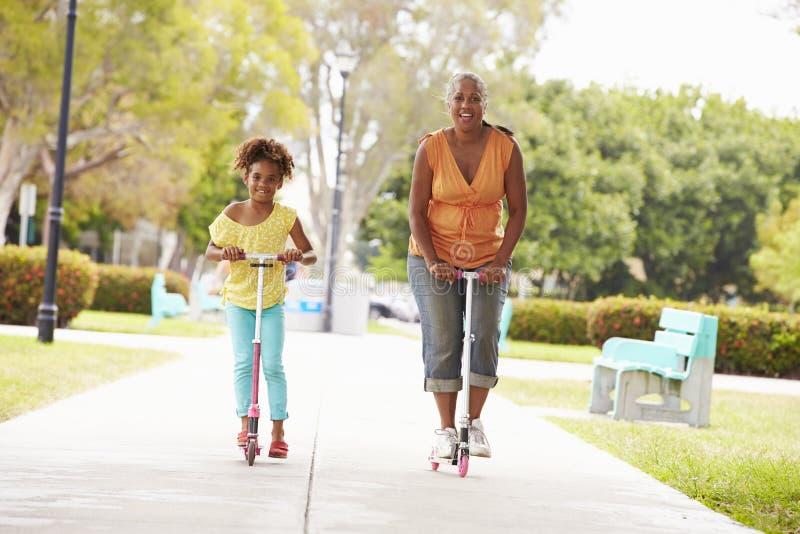 祖母和孙女骑马滑行车在公园 免版税库存照片