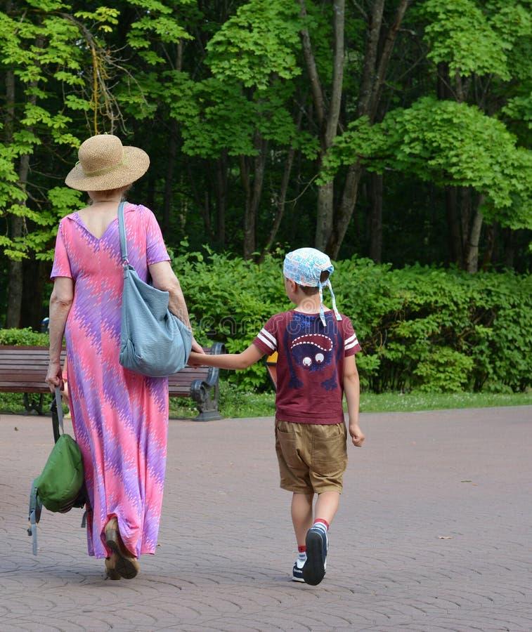 祖母和孙子步行在绿色夏天公园在米斯克白俄罗斯 免版税库存照片