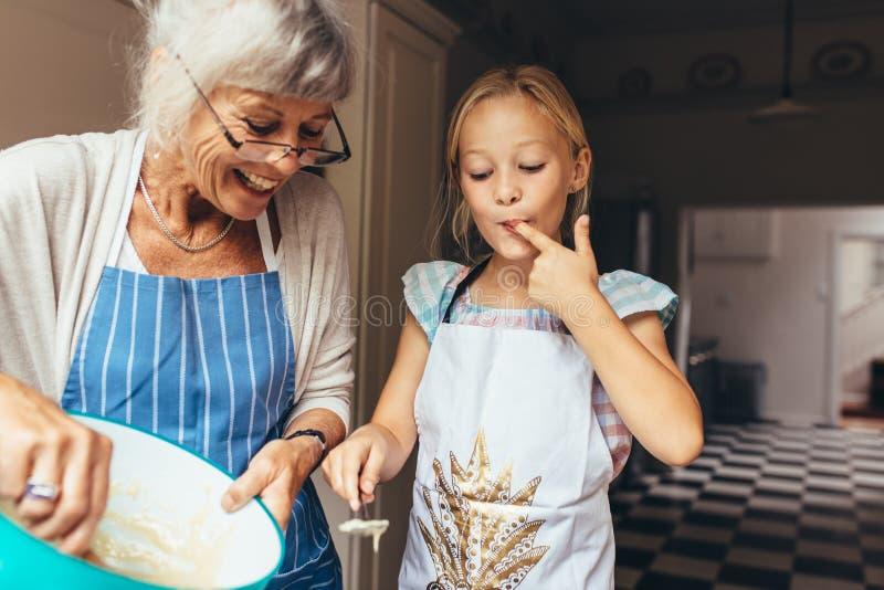 祖母和孩子获得做蛋糕的乐趣在厨房 库存图片