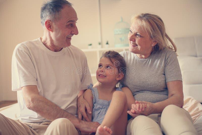 祖母和祖父坐床与他们的孙女一起 库存图片