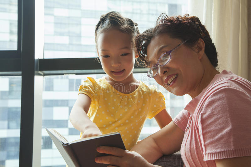 祖母对她的孙女的阅读书 库存图片