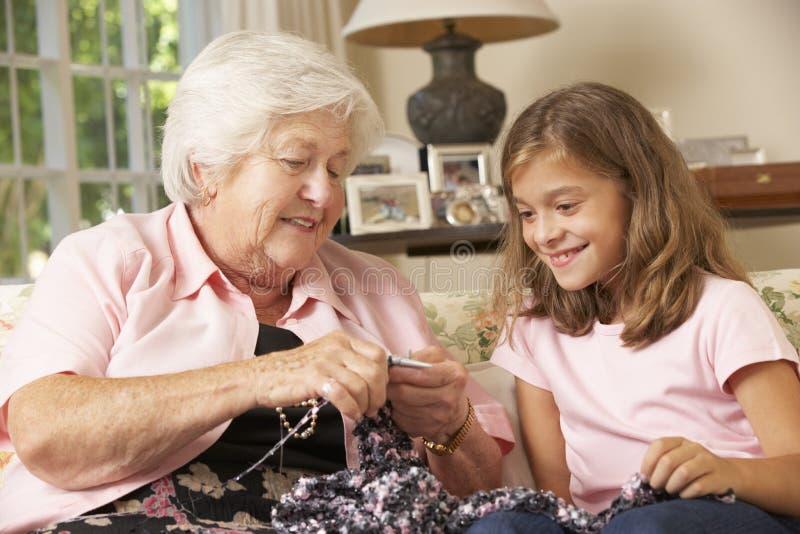 祖母显示孙女如何在家编织 免版税图库摄影
