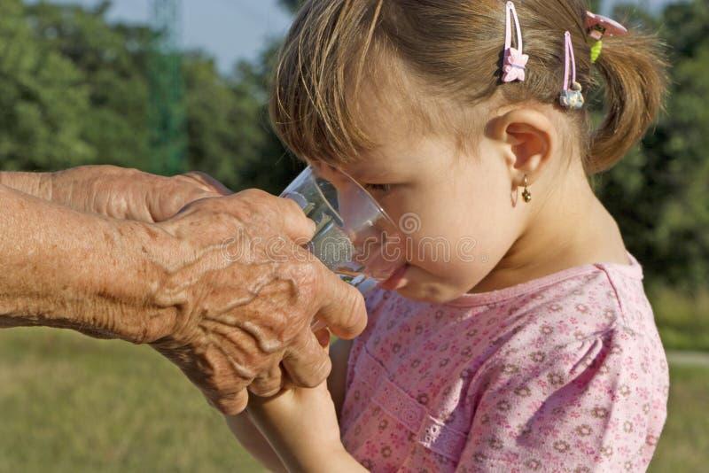 祖母的手有杯的孙女的水 免版税图库摄影