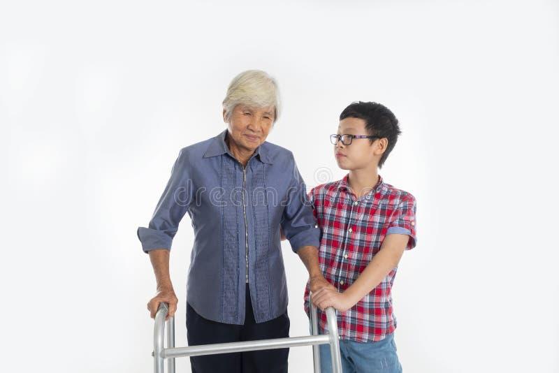 祖母资深妇女和孙子有使用的一个步行者在期间 免版税图库摄影