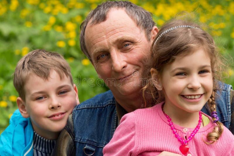 祖父、孙女和孙子微笑 免版税库存图片