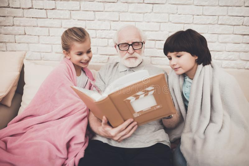 祖父、孙子和孙女在家 祖父和孩子观看在册页的照片 免版税图库摄影